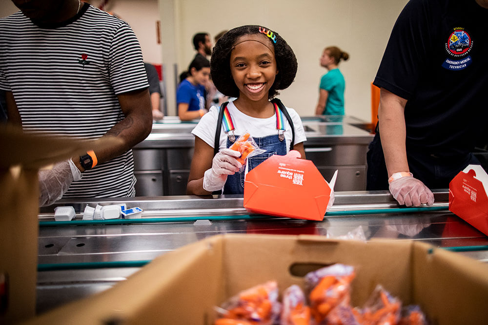 A young girl volunteer helps prepare food boxes in an assembly line.
