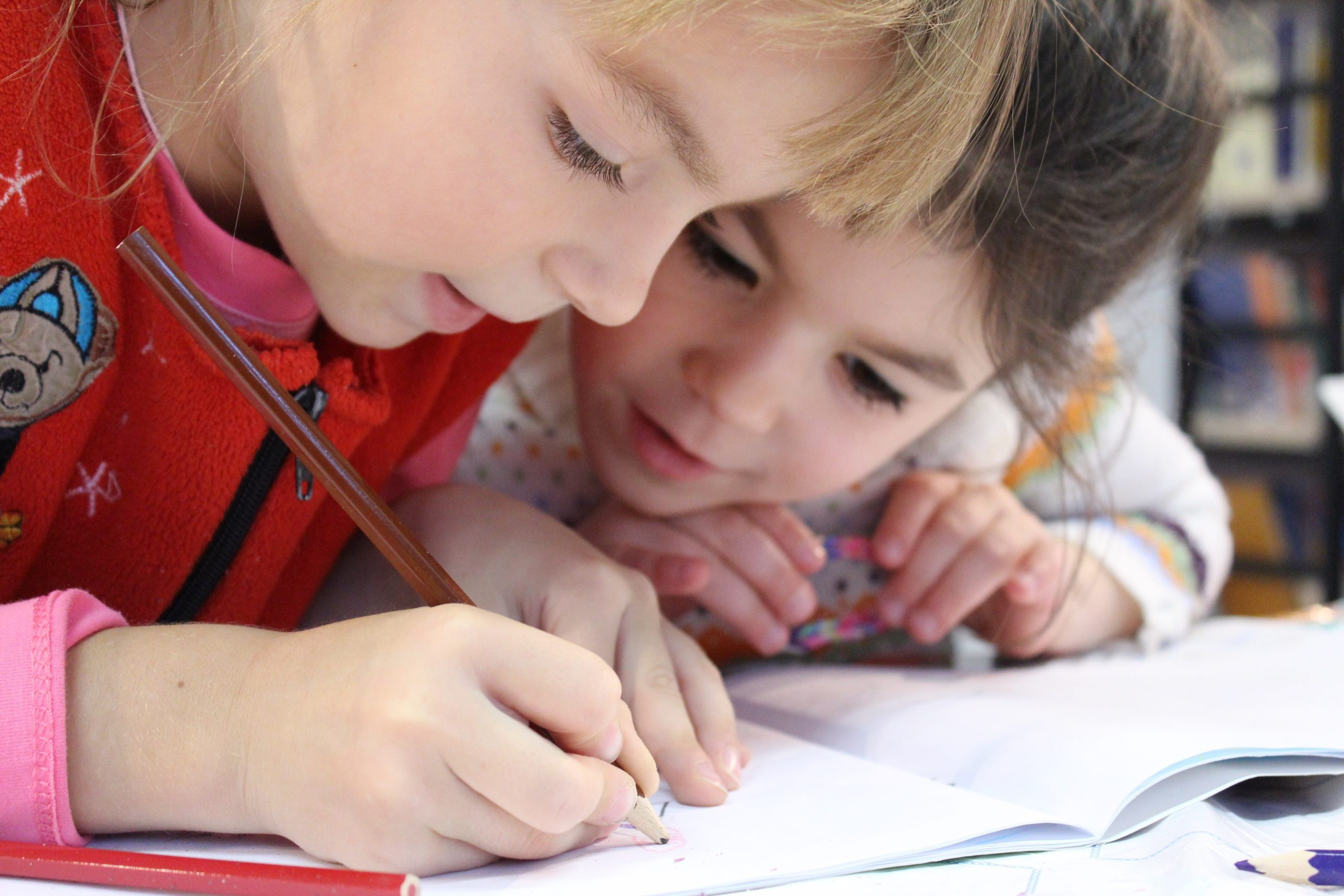 Two small children work on homework together