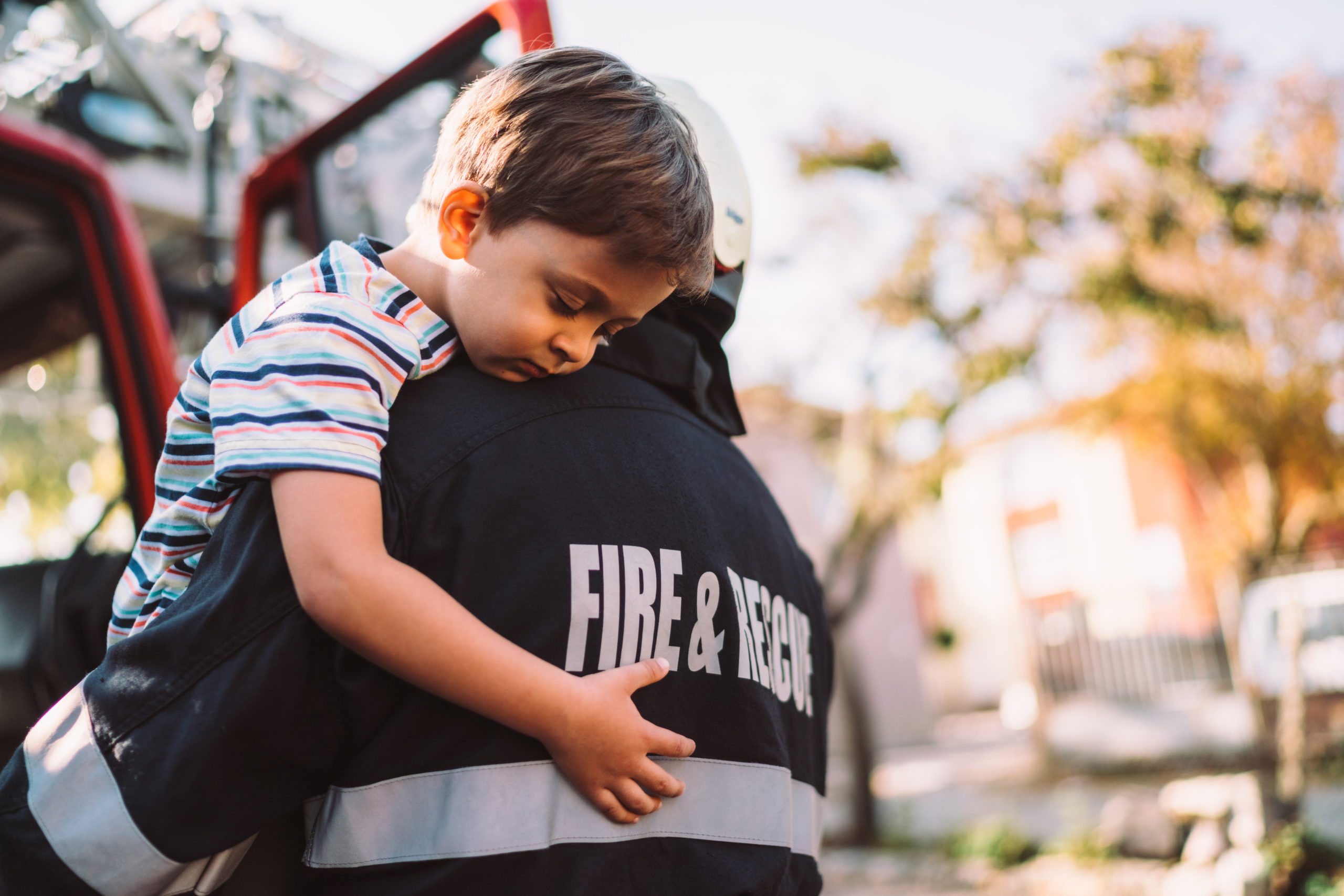 Firefighter carrying little boy after successful rescue operation