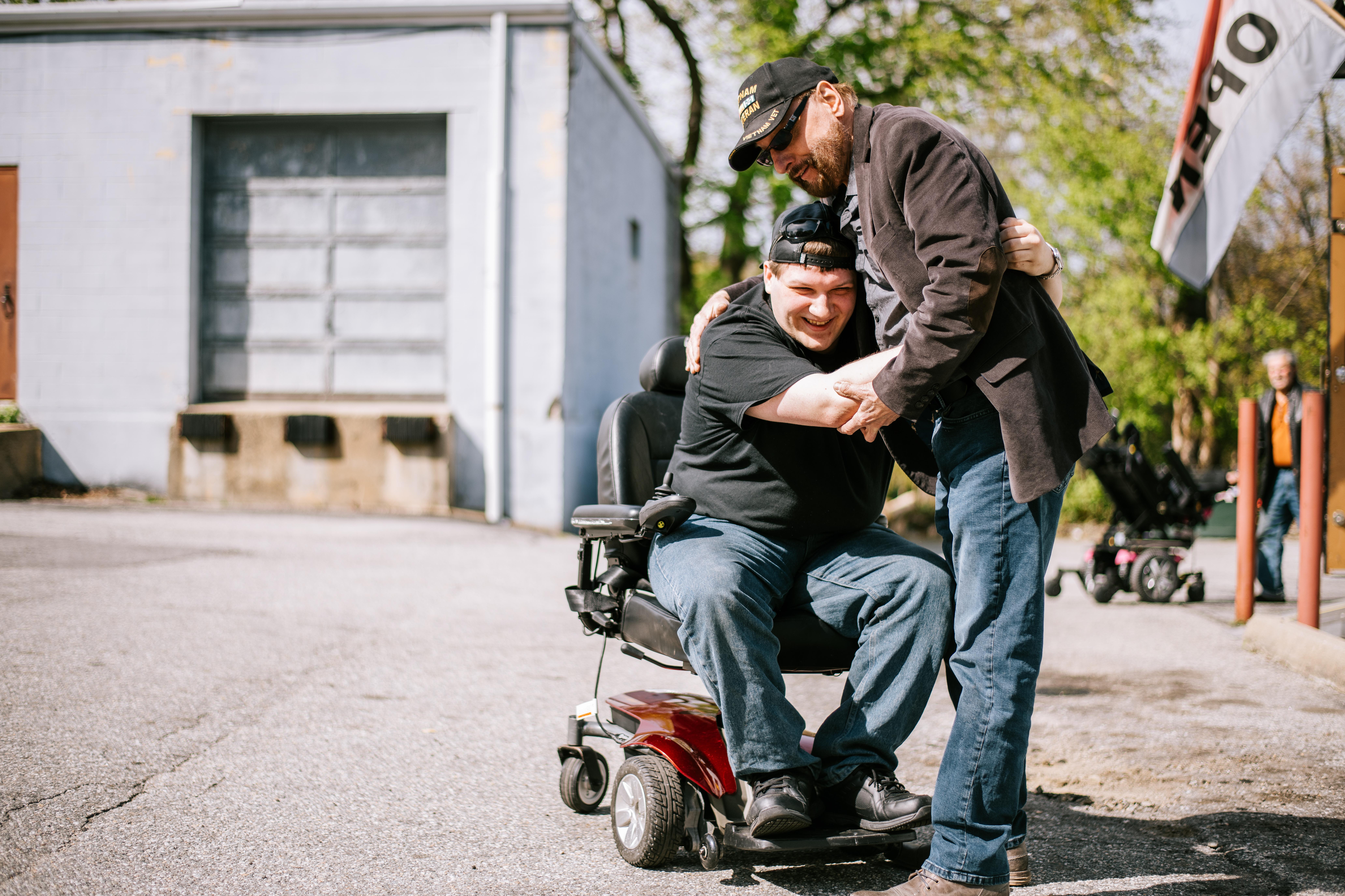 An older man hugs a man in a wheelchair