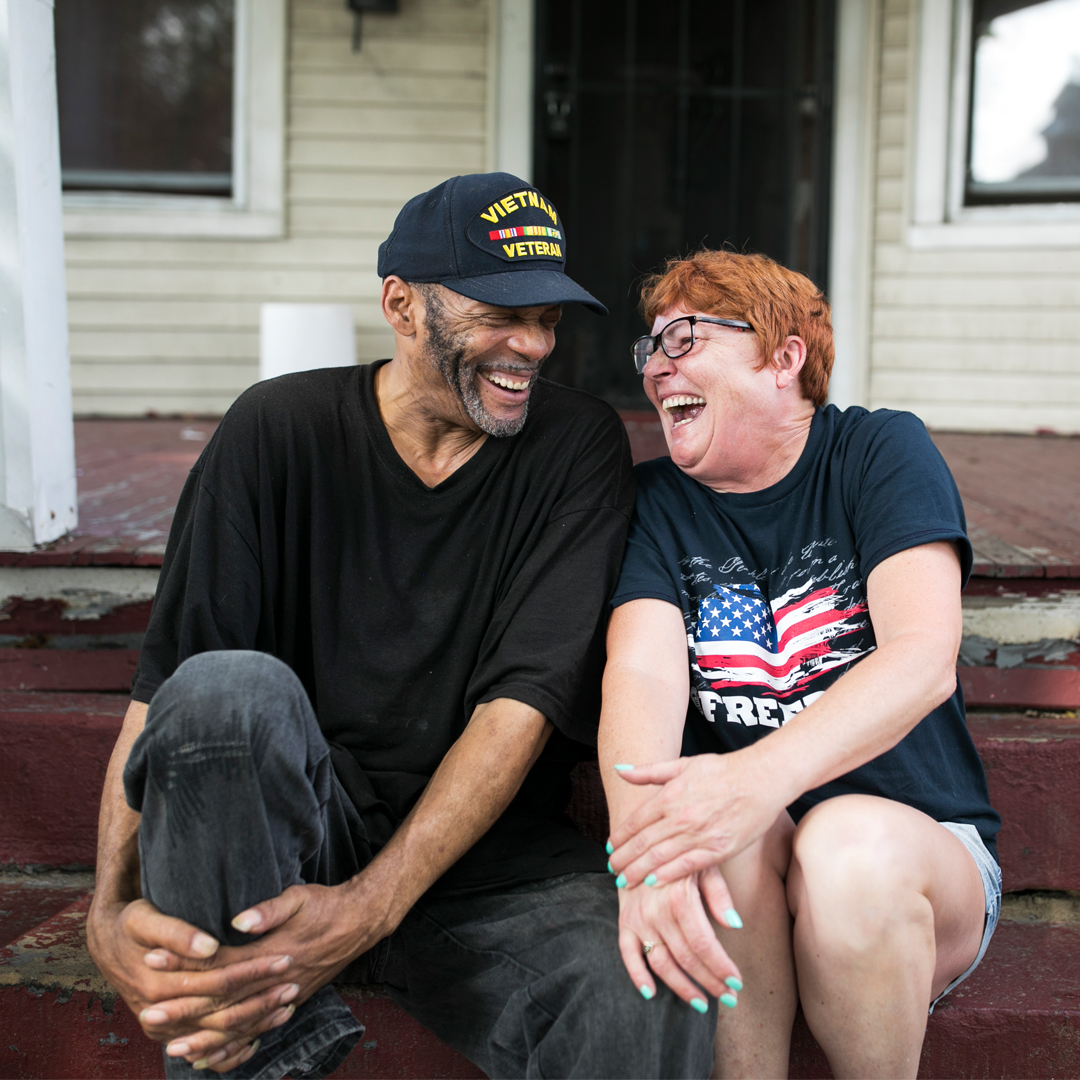 a man with a veteran hat on and a woman with an American flag shirt sitting on front porch stairs laughing