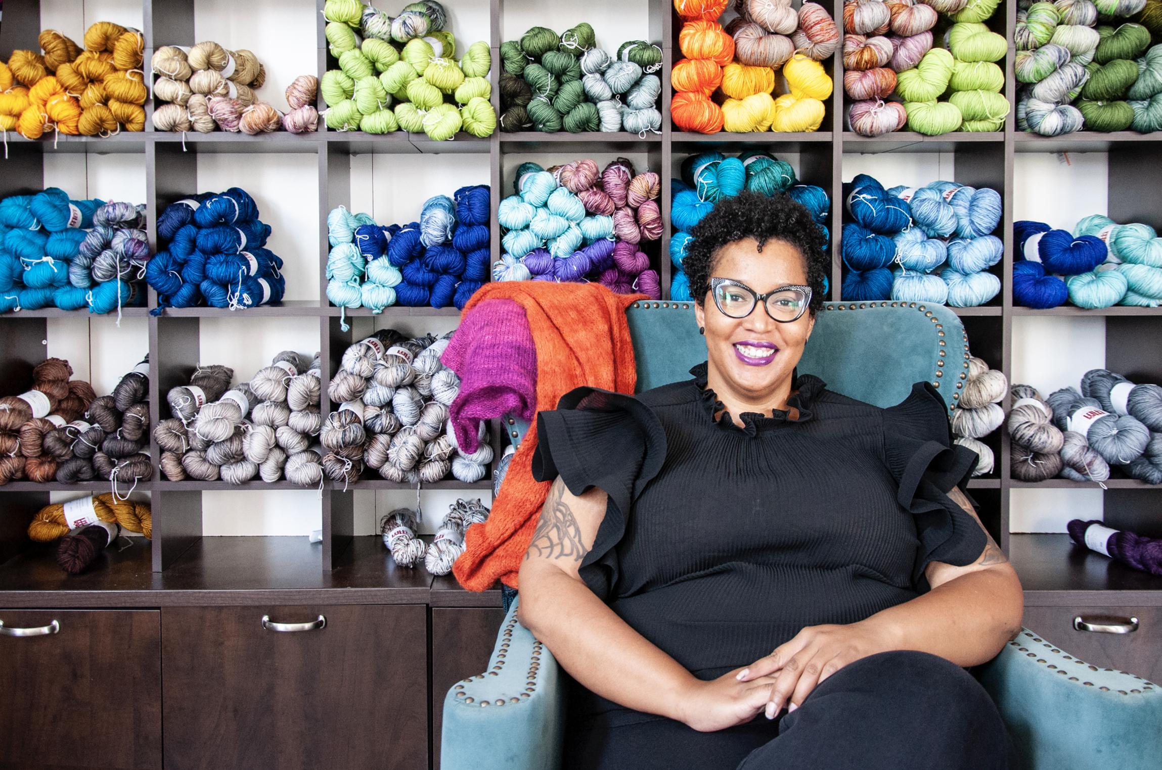 Karida Collins sitting in front of yarn