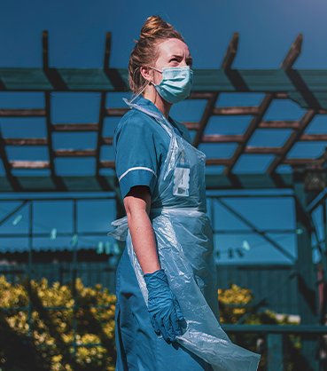 woman wearing a blue mask and a blue surgical apron