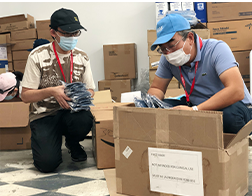 two men packing boxes full of masks