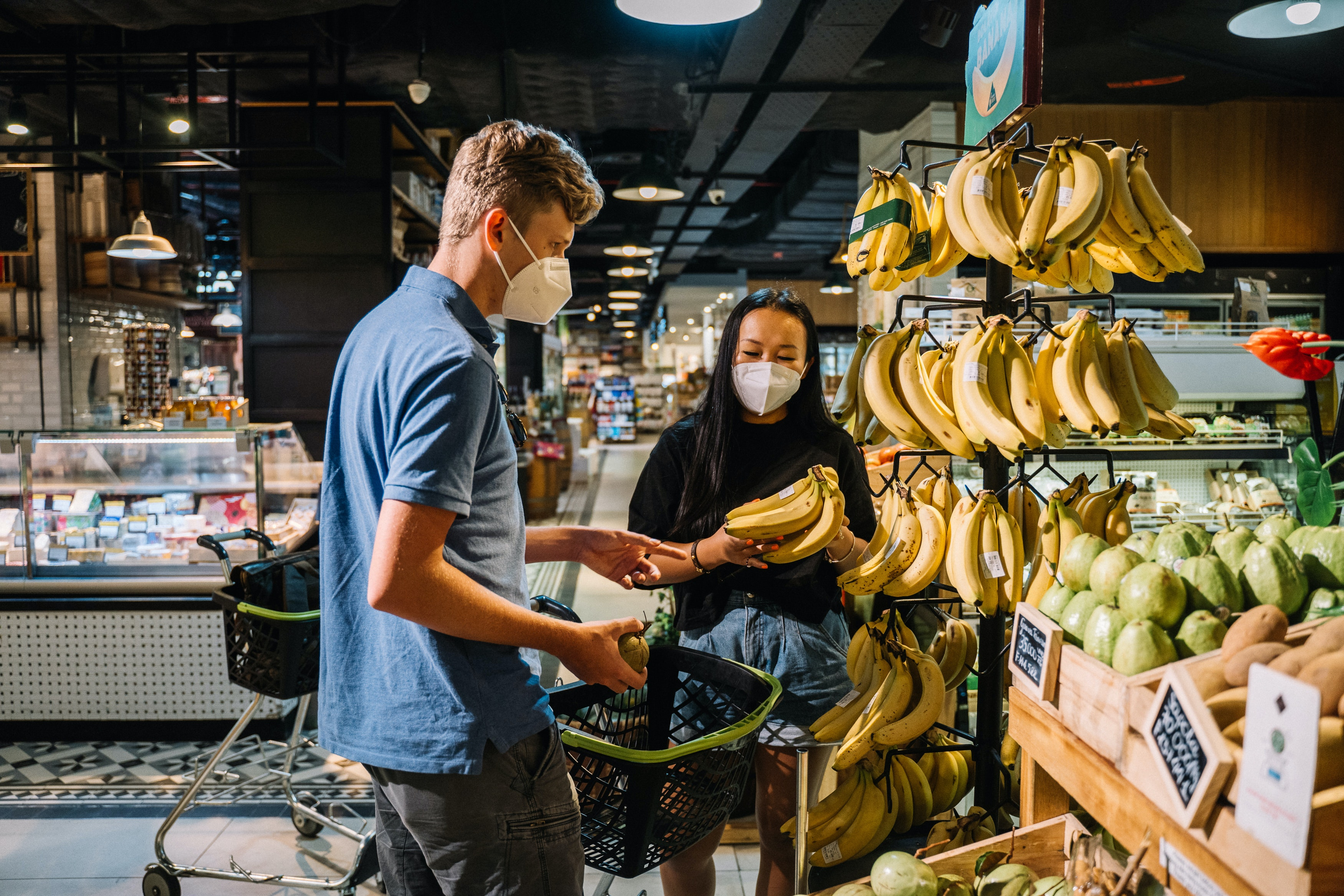 A man and woman wearing masks in the grocery store