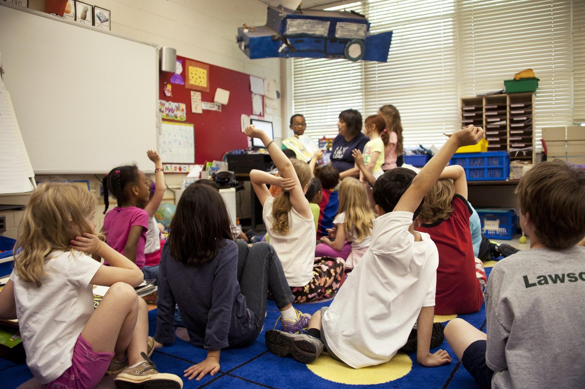 preschoolers raising their hands in a classroom