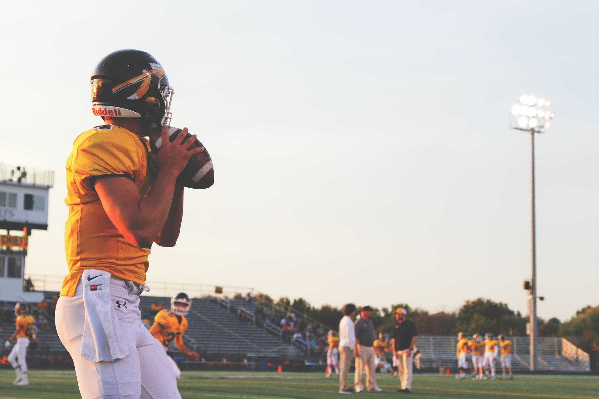 football quarterback wearing a yellow uniform holding a football