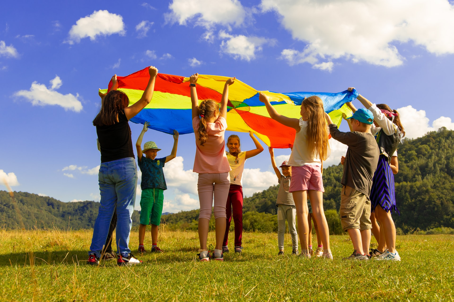 kids playing a game outside with a big parachute tarp