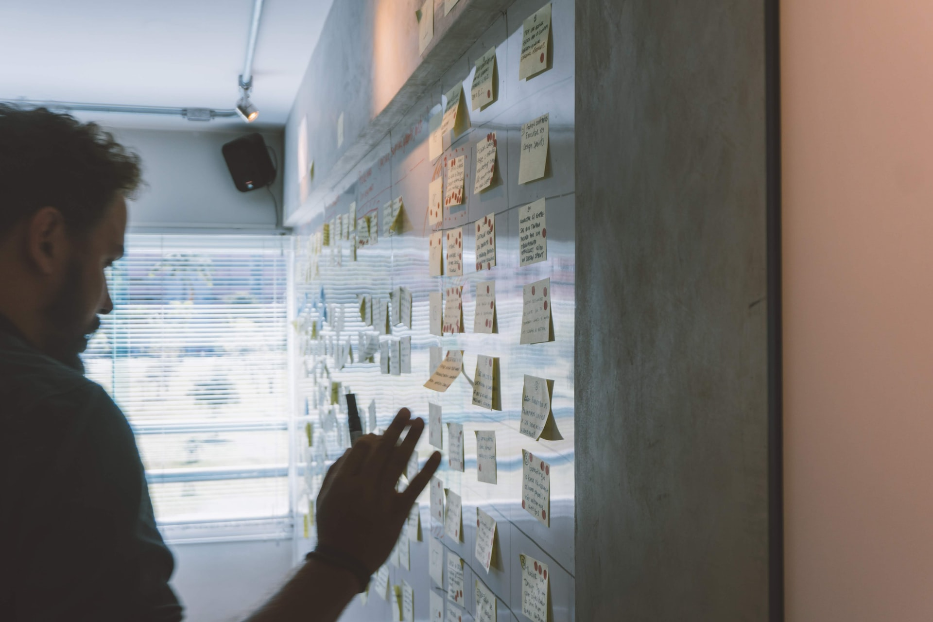 man putting sticky notes on a wall