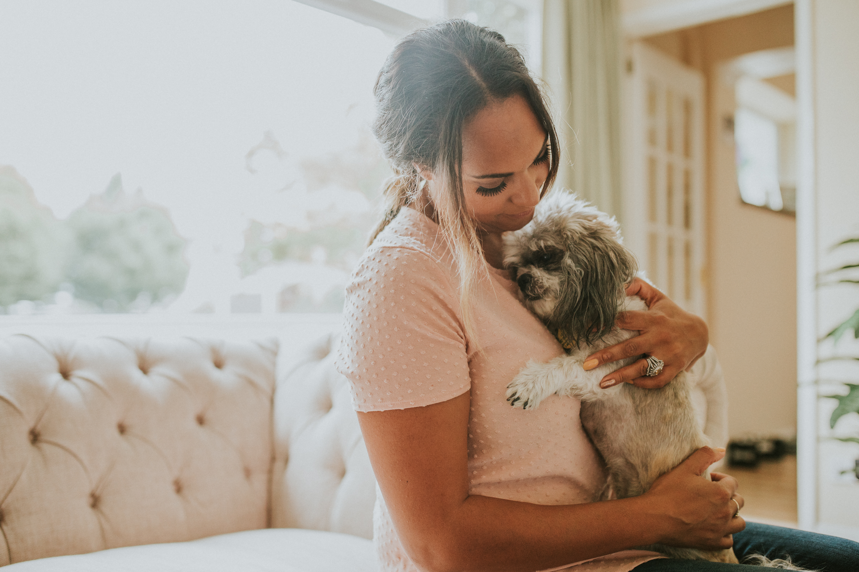 a woman holding her dog lovingly