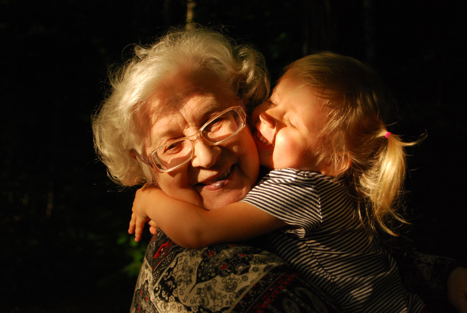 a grandmother and granddaughter hugging and smiling
