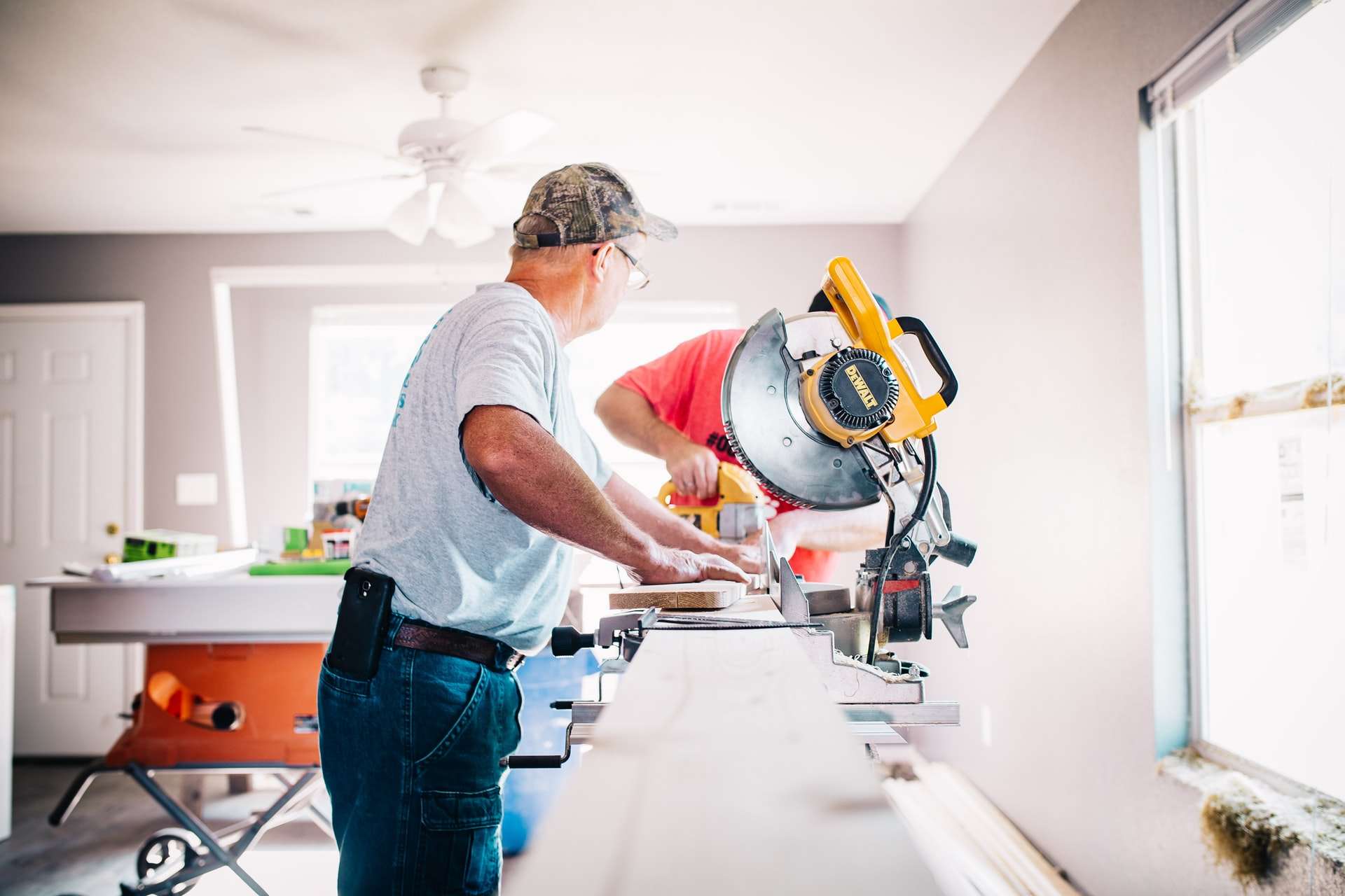 Man cutting a piece of wood with a saw