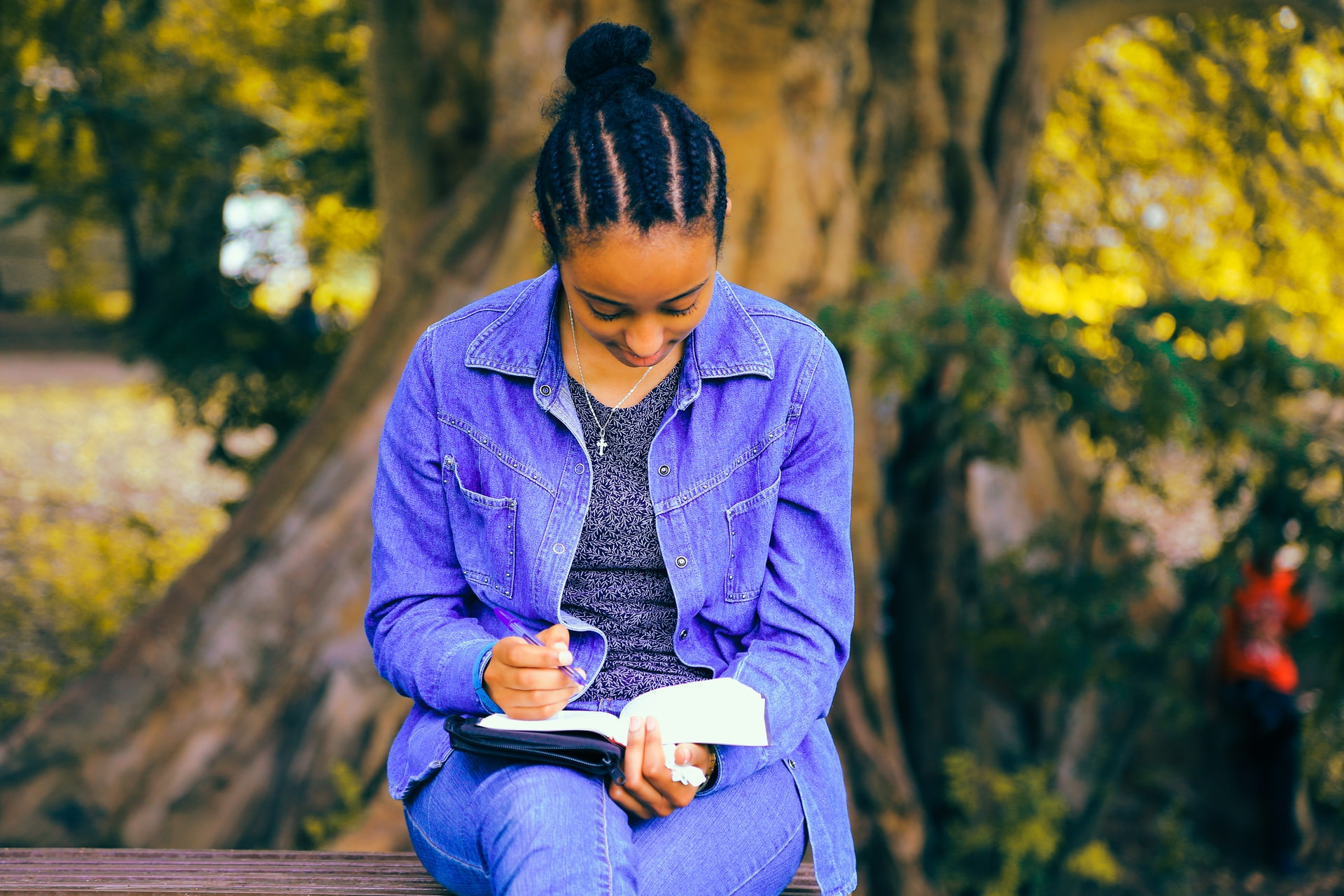 A Black woman wearing a blue shirt sitting on a bench and writing in a journal