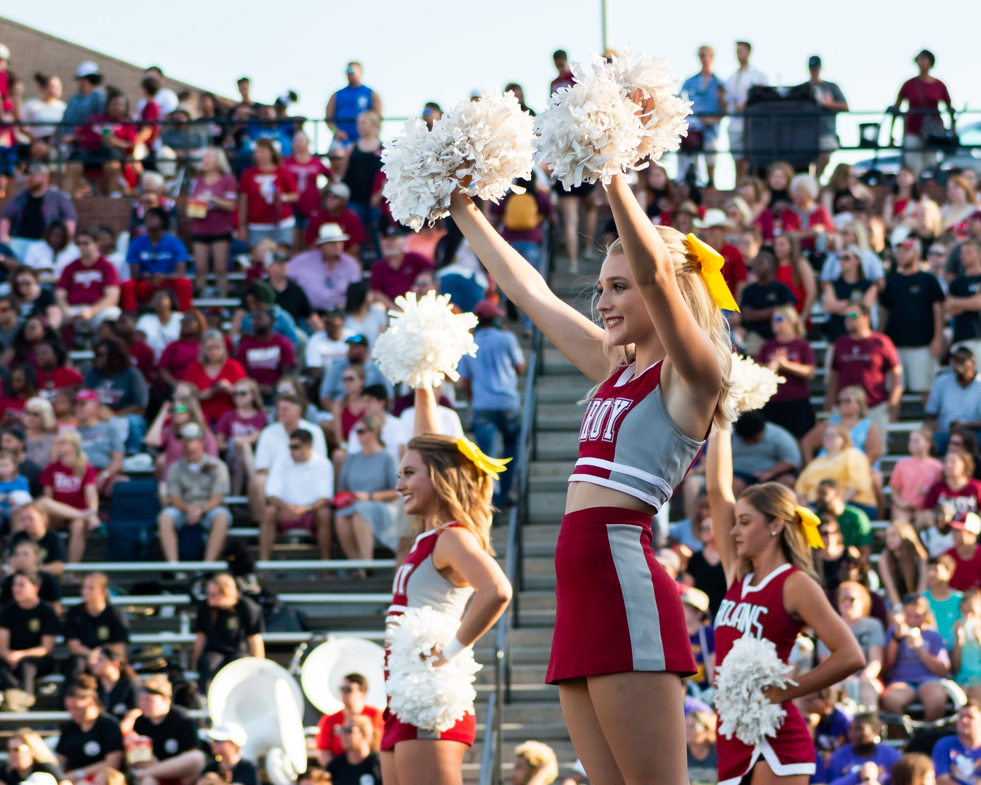 cheerleader wearing a red and gray uniform holding up pom poms with a crowd behind her