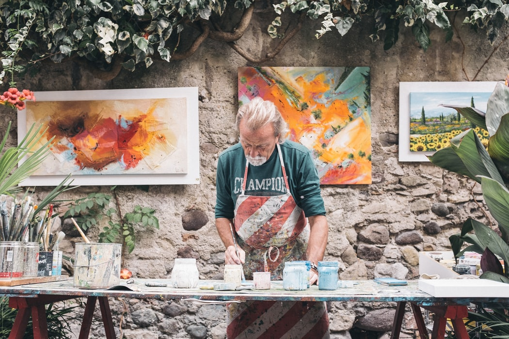 older man painting pottery
