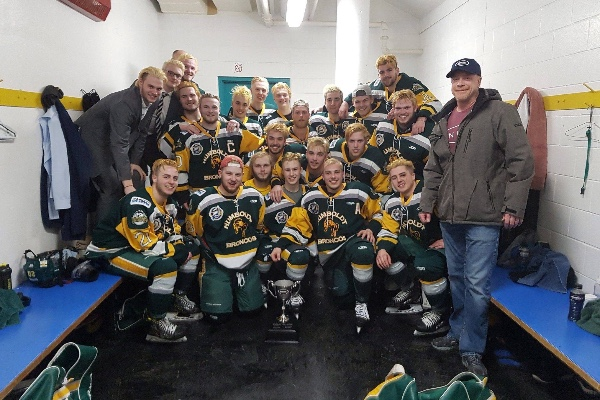 Humboldt Broncos hockey team poses for a photo in a locker room