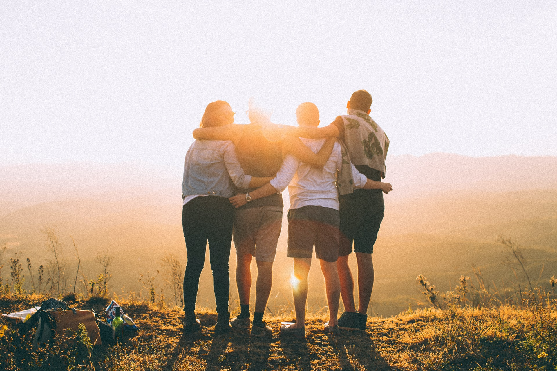 four friends with their arms around each other looking out