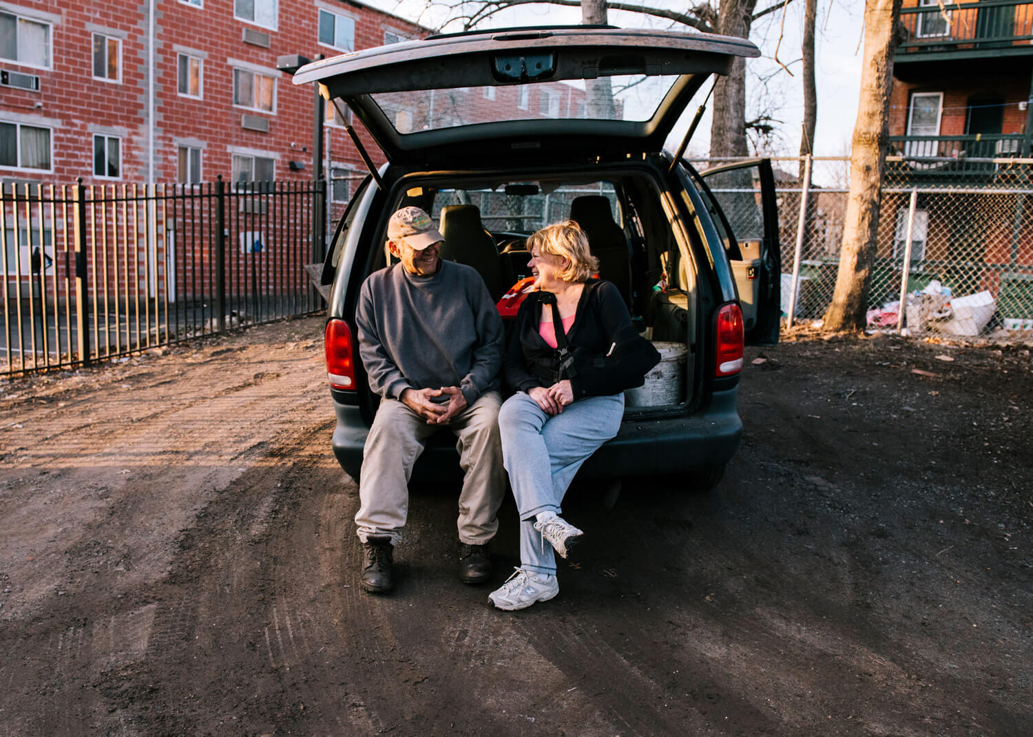 man and woman sitting in the back of a van