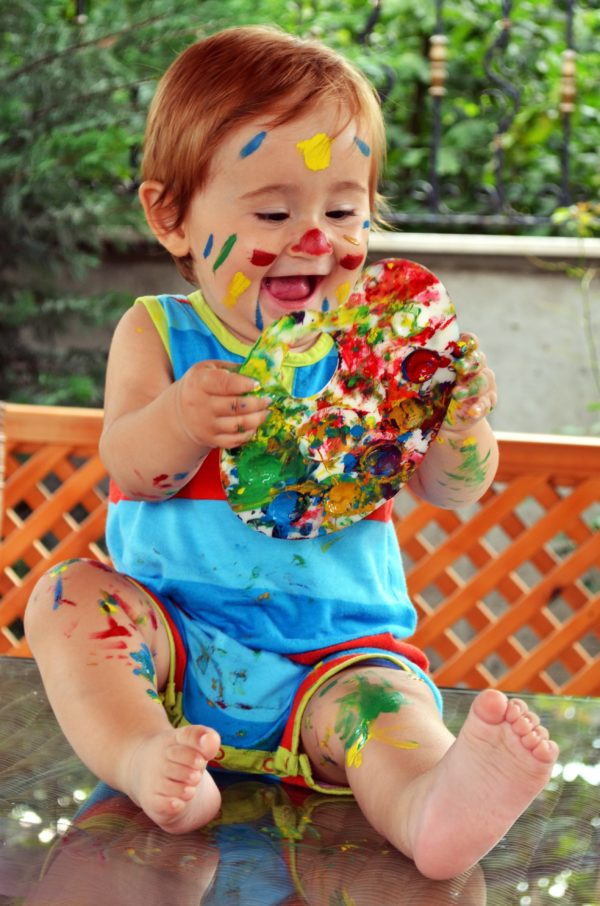 Baby smiling and covered in paint