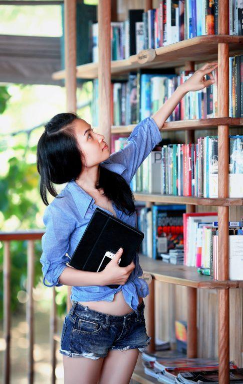 girl placing books on a bookshelf