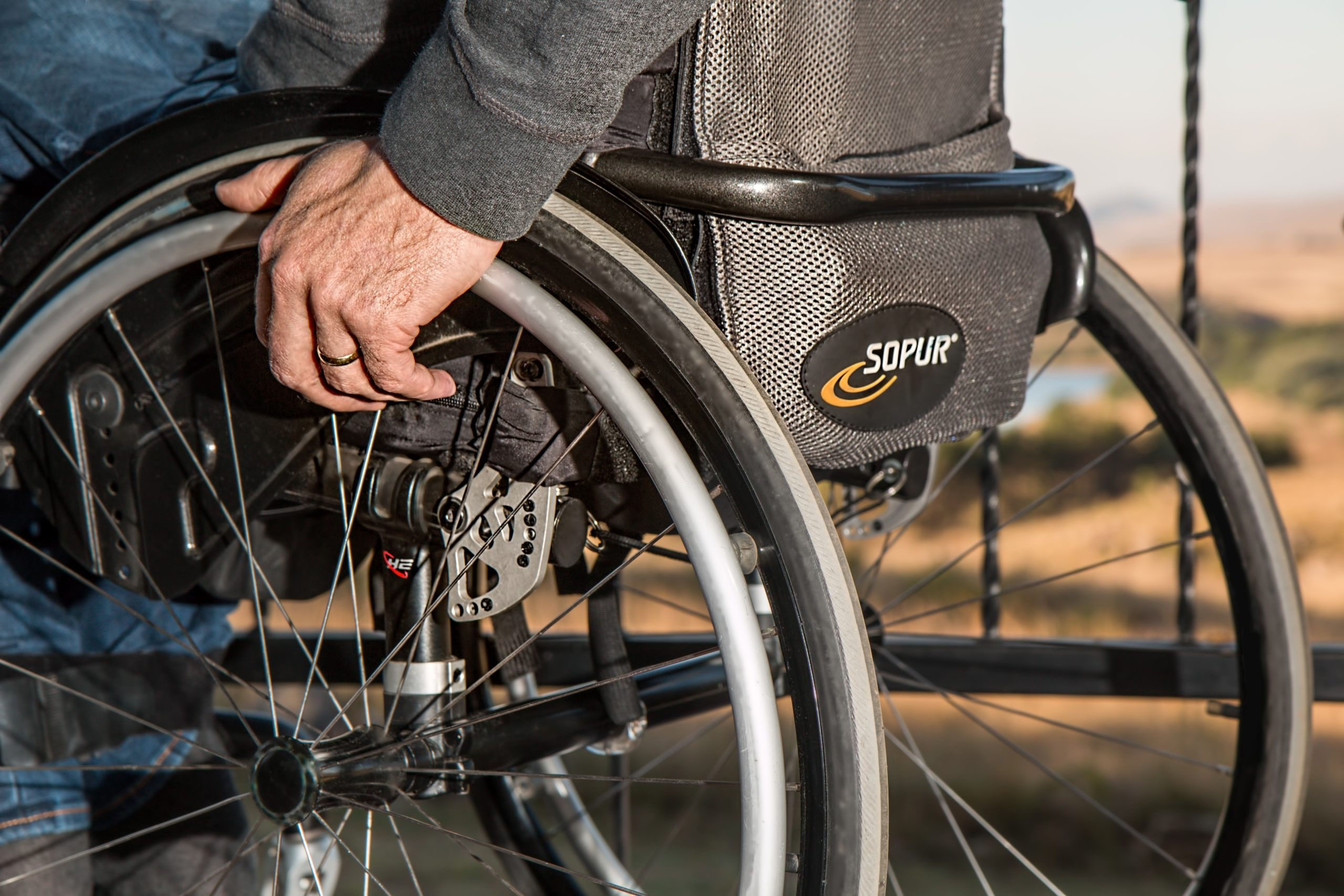 person with hand on wheelchair