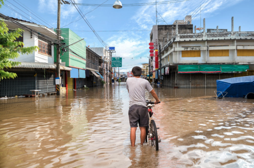 man standing in flood water with a bicycle
