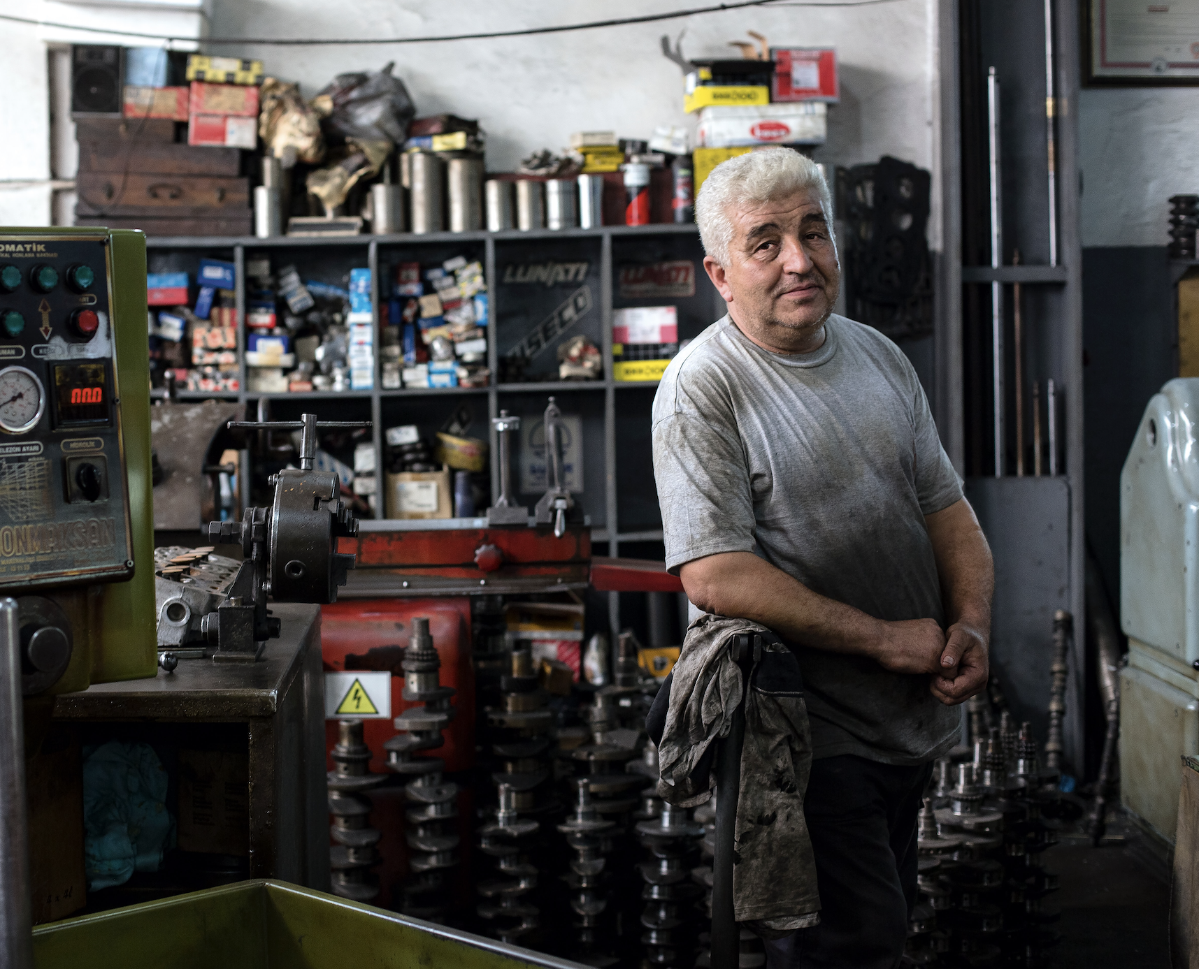 A mechanic poses for the camera in his garage