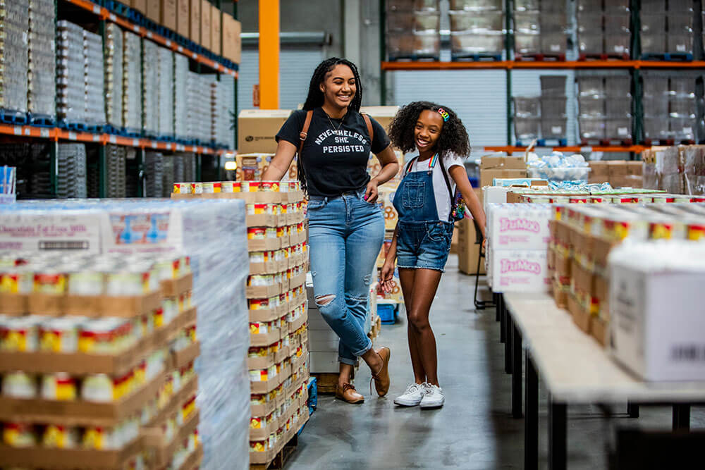 A mother and daughter stand together in a food bank