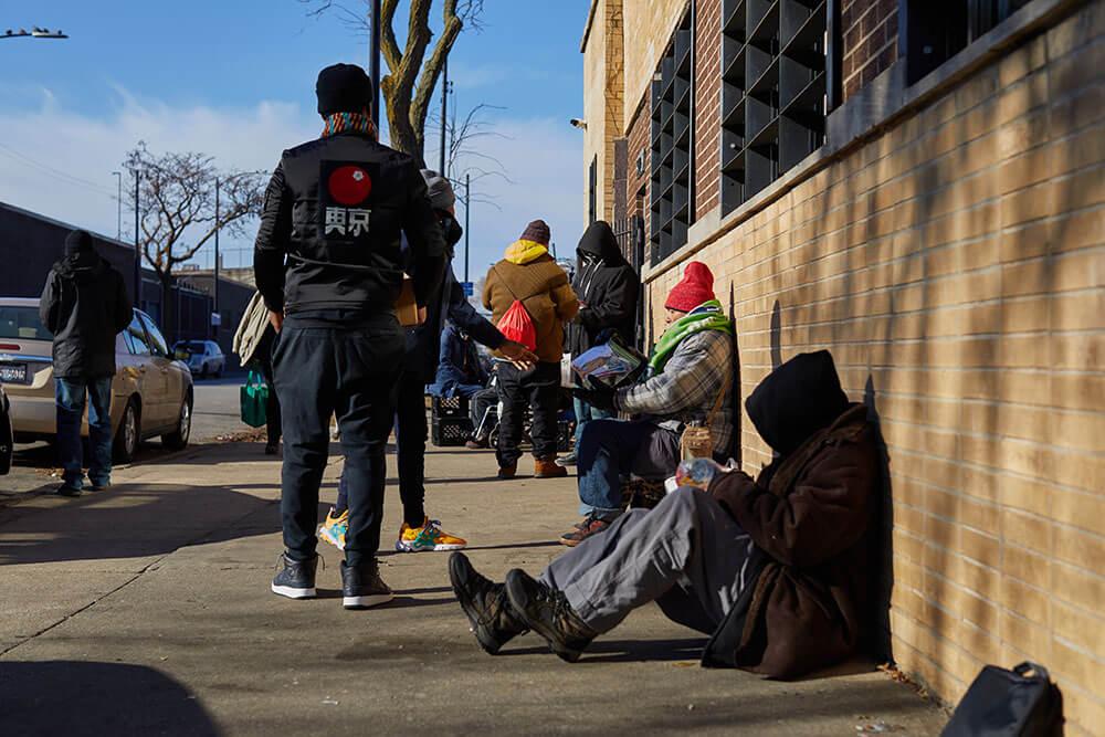 Homeless men sitting on the sidewalk