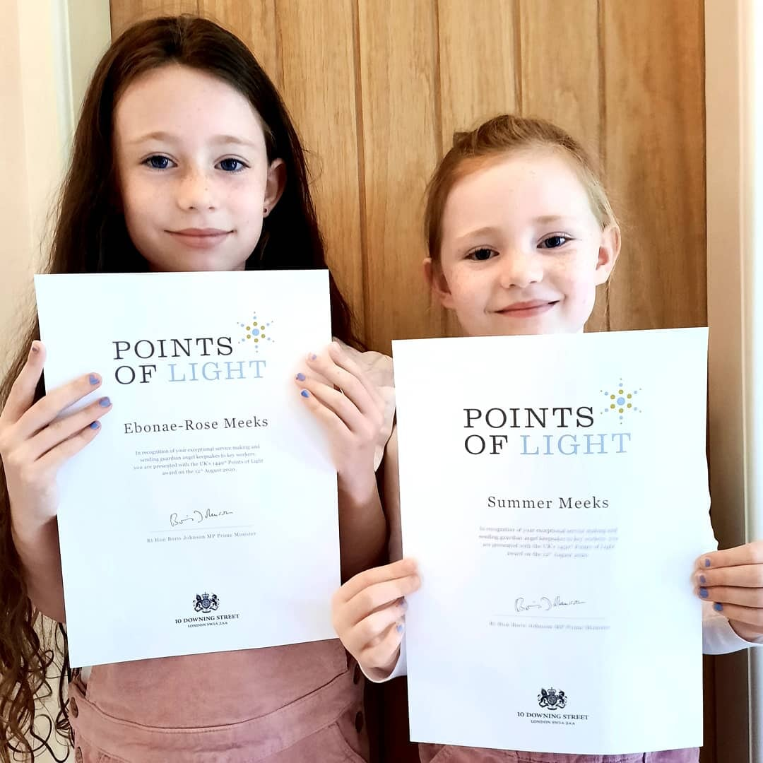 Sisters hold up their Point of Life certificates