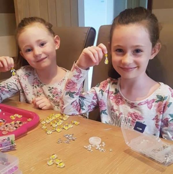 Girls hold up their home-made guardian angels