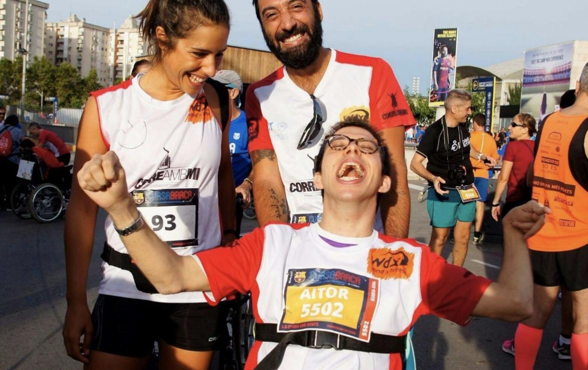 Niño en silla de ruedas y adultos participando en un maratón