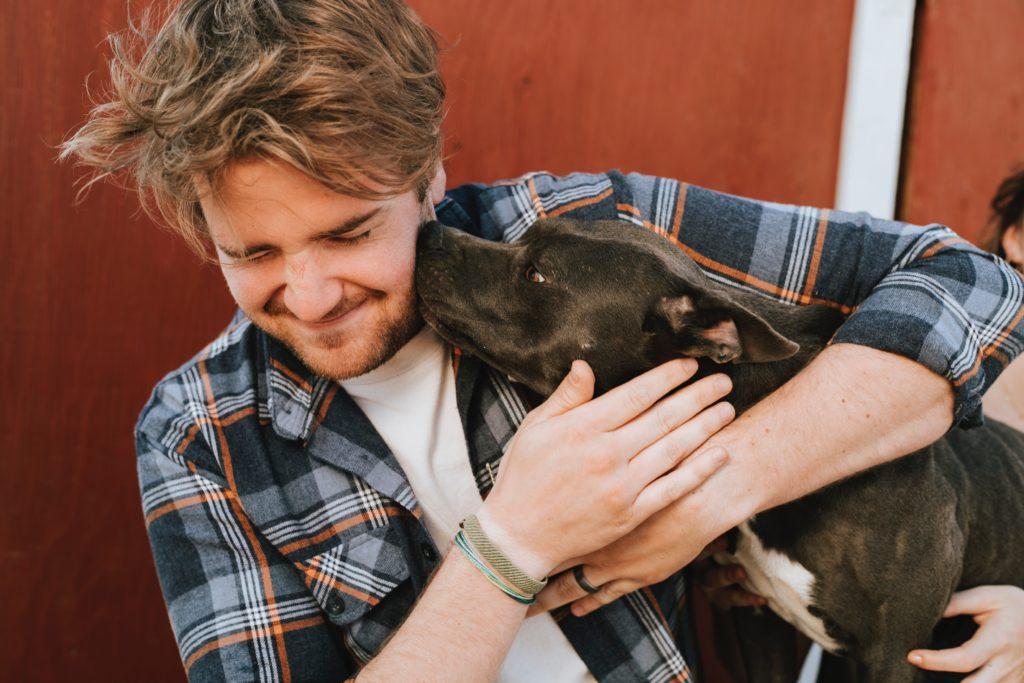 Homme embrassant son chien