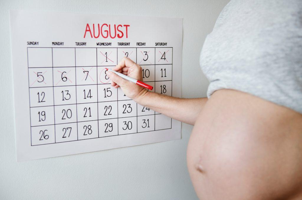 Femme enceinte écrivant sur un calendrier