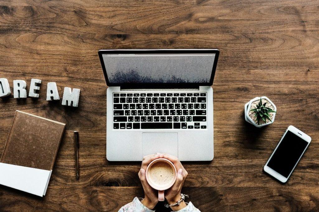 Ordinateur portable sur un bureau avec deux mains tenant un café