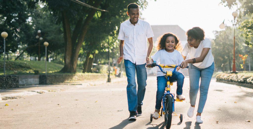 parents qui apprennent à leur enfant à faire du vélo