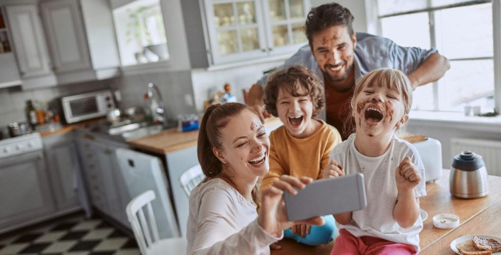 Couple avec ses enfants prenant un selfie dans la cuisine