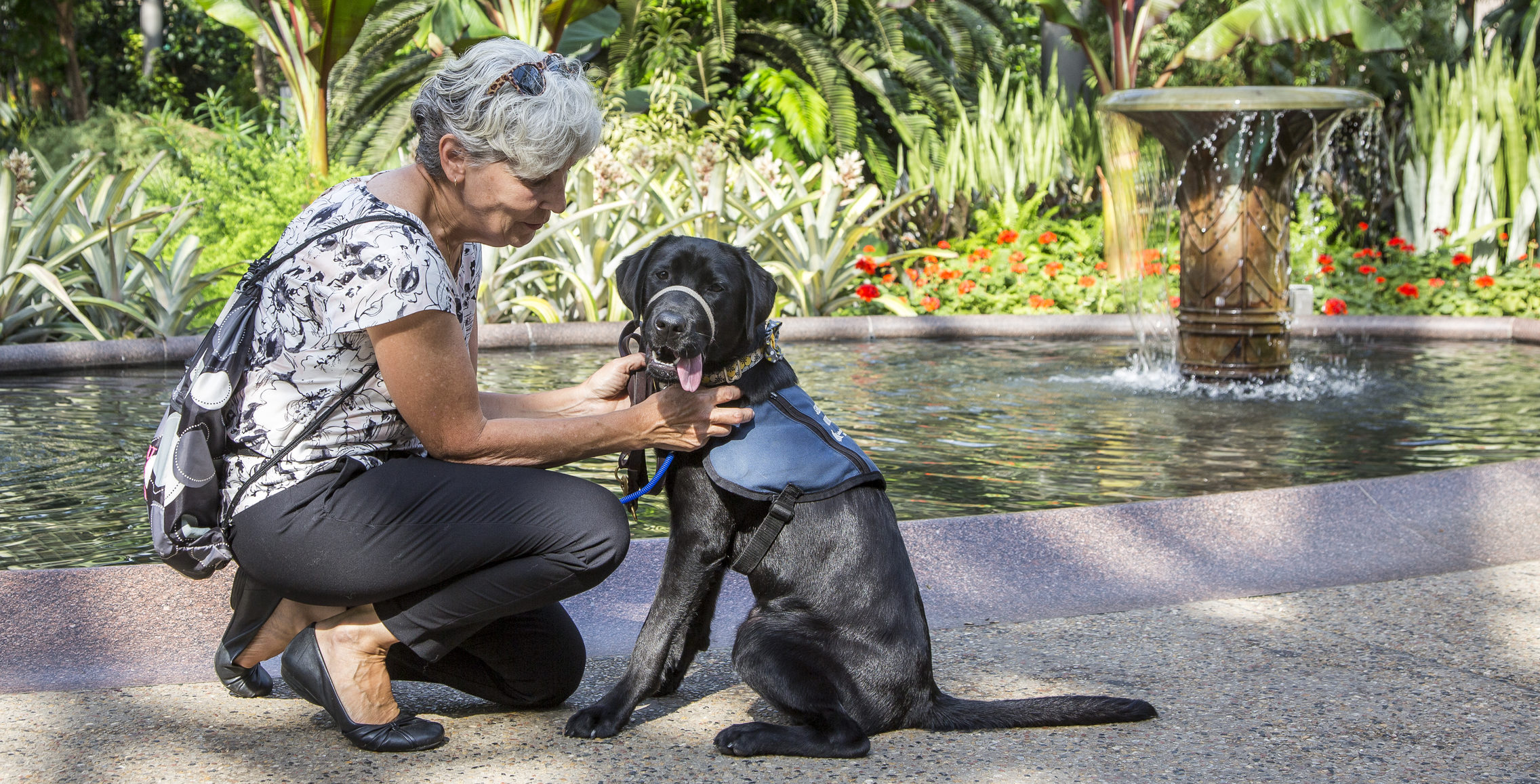 woman kneeling with service dog