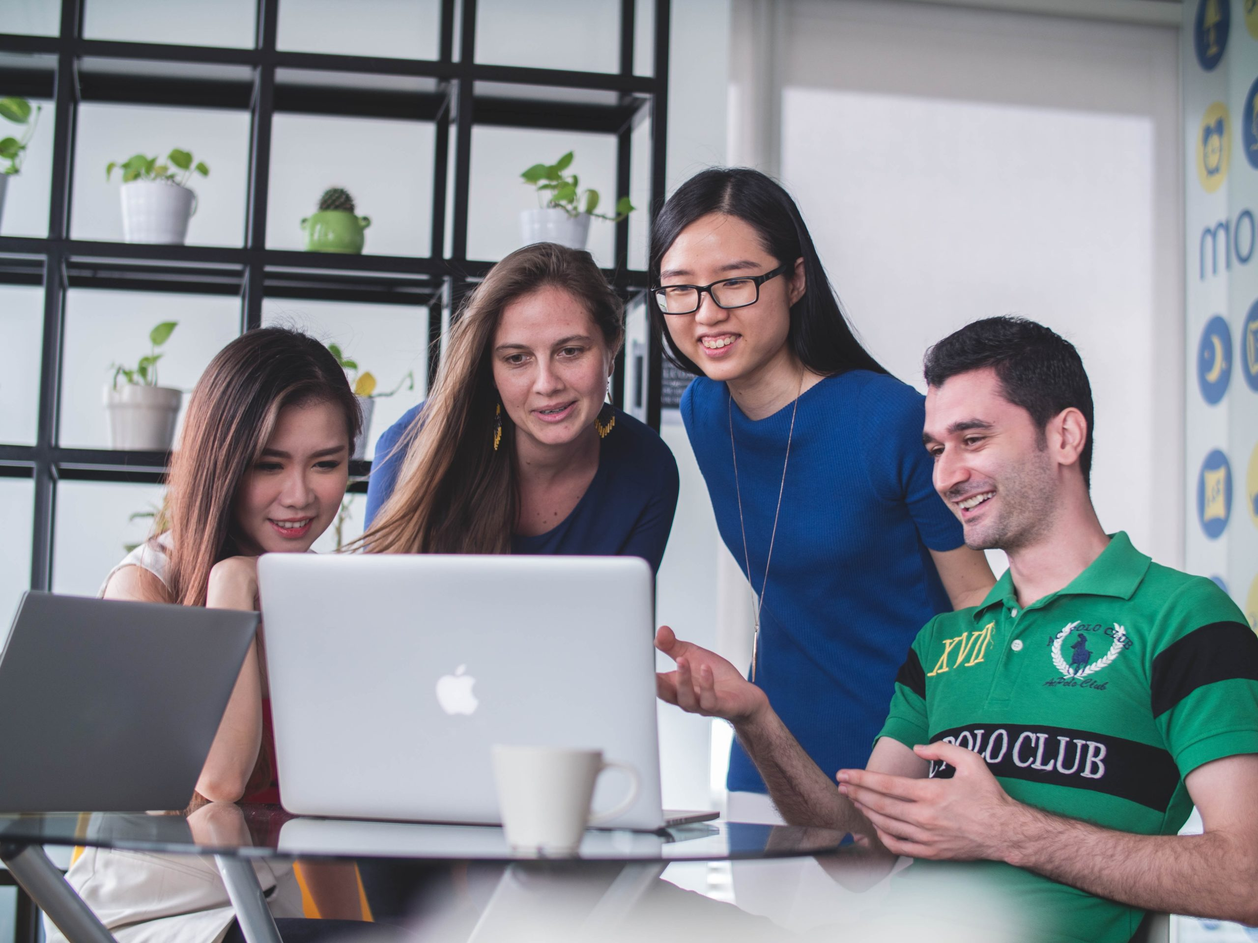 Four people in an office looking at a laptop screen and smiling