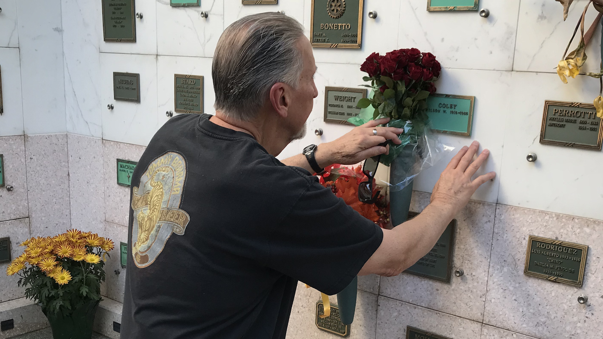 Man putting flowers on a grave