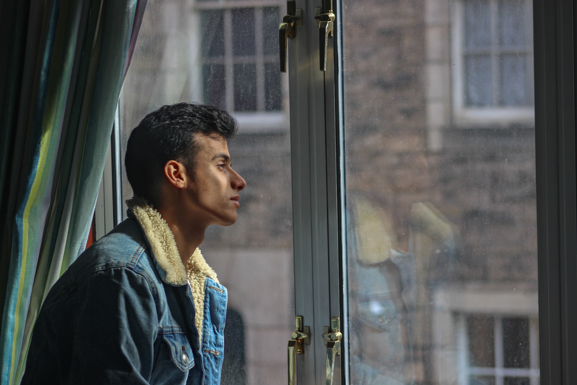 young man looking out of a window
