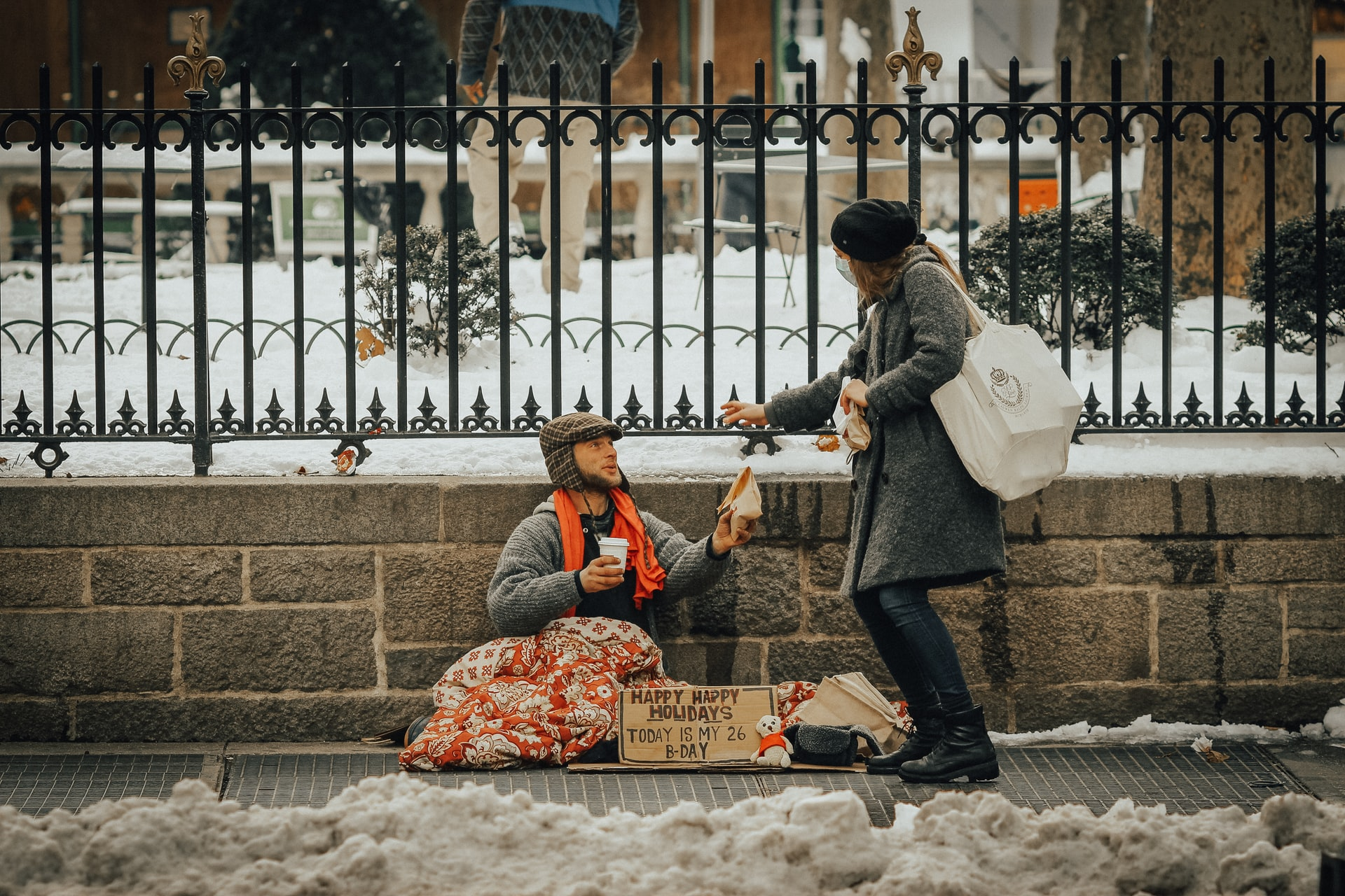 woman giving food to a man experiencing homelessness