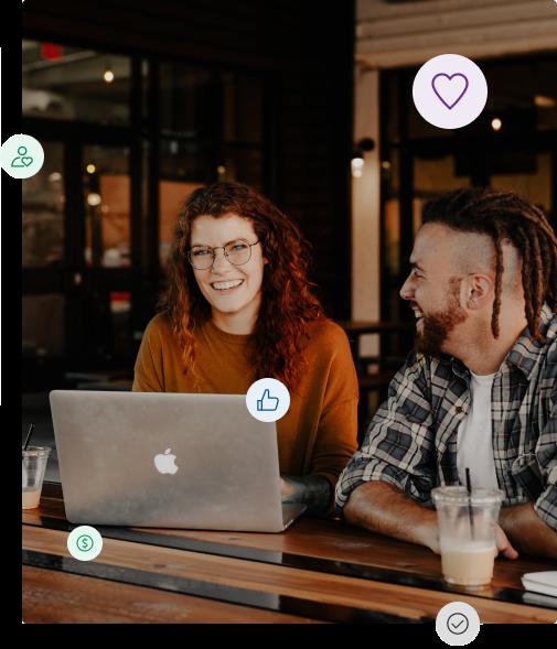 Smiling man at woman sitting at laptop
